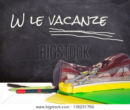 Tools for school: pencil case pens notebooks with lively writing on the blackboard the holidays