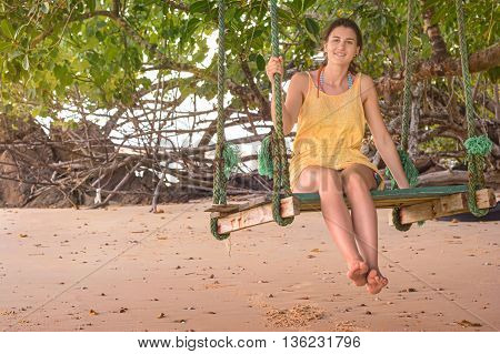 Young woman happy on the beach swing