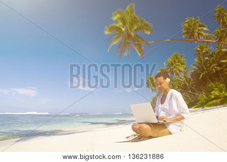 Young woman on her laptop by the beach.
