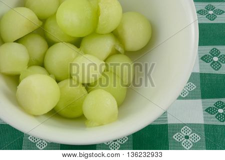 Honeydew melon balls in white bowl on tablecloth