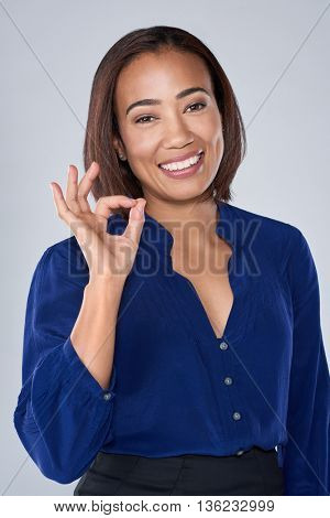 Happy smiling businesswoman holding up OK hand gesture, isolated in studio