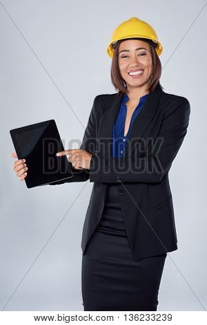 Mixed race woman in suit hardhat and electronic tablet, engineer consultant construction surveyor careers industry technology