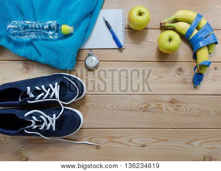 Fitness concept with sneakers. towel bottle of water measure tape fruit and a stopwatch