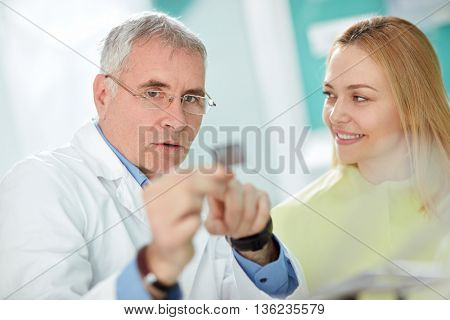 Male dentist explains to female patient problem with tooth using dental film