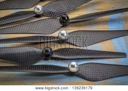 a set of carbon fiber propellers for a drone against grunge wood