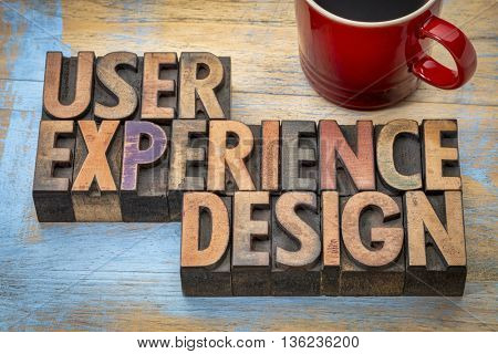 user experience design - word abstract in vintage letterpress wood type with a cup of coffee