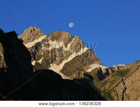Morning scene in the Swiss Alps. Mt Altmann. Moon.