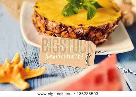 a brown cardboard label with the text happy summer, a starfish, some slices of pineapple and a piece of watermelon on a blue rustic wooden surface