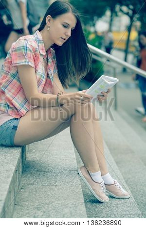 Girl student reads the notes sitting on the stairs. Toned photo