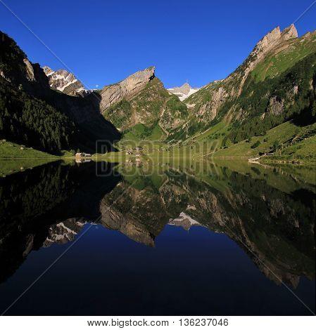 Quiet summer morning at lake Seealpsee. Alpstein Range mirroring on the water.