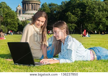 two friends with tablet computer sitting on the grass in the summer park. youth lifestyle