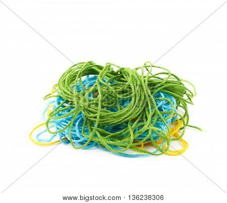 Mixed pile of colorful yarn threads isolated over the white background