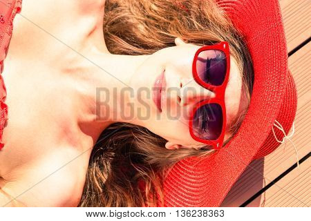 Glamorous young woman sun tanning at pool deck - Beautiful girl sunbathing close-up of face view from above - Concept of beauty and skin care to prevent sunburn during summer holiday