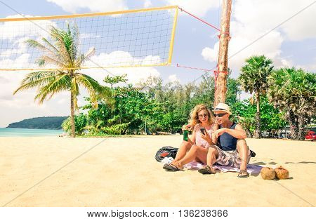 Tourist couple using mobile phone on the beach at Phuket Island - Travel friends looking holiday pictures sitting on the white sand - Concept of relax and technology in a tropical destination tour