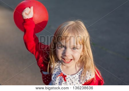 smile little girl plays with red ball