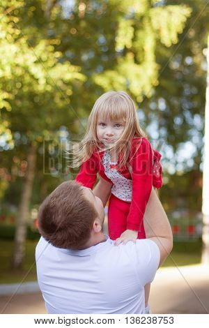 Father holding little daughter in air .