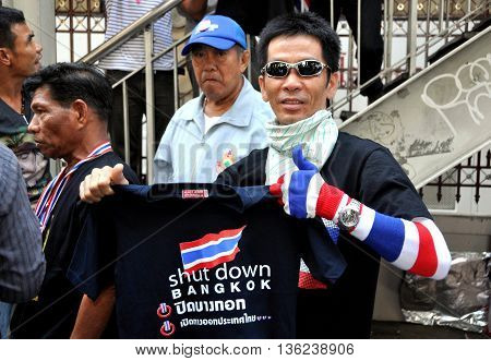 Bangkok Thailand - January 13 2014: Thai man holding up a Shut Down Bangkok tee-shirt on Day 2 of the anti-government protests rocking the capitol city