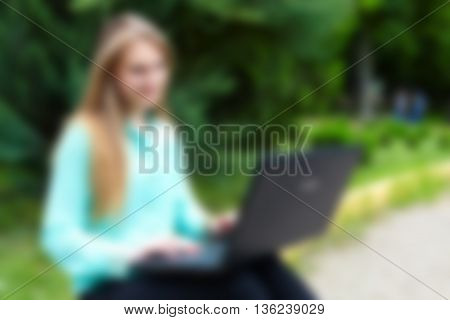 Beautiful woman working with a laptop. Fuzzy photo. Blur