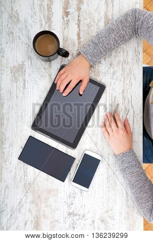 A woman using Electronics on a desktop.