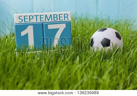 September 17th. Image of september 17 wooden color calendar on green grass lawn background. Autumn day. Empty space for text.