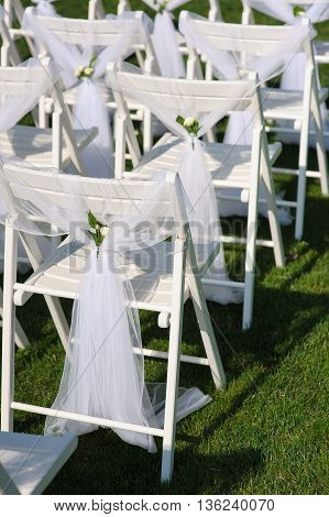 White decorated chairs on a green lawn. Chairs set in rows for the wedding ceremony. They are decorated for the festive event. Chairs are on the green lawn outside.