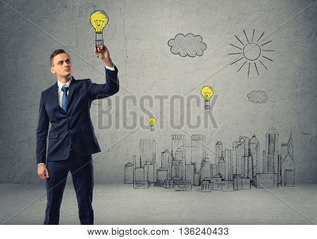 Businessman draws bulb-parachute over sketch of city. Inspired by the idea. Business concept. Business idea. Inspiration. Success and development. Good idea is the way to wealth and success.