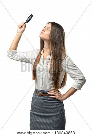 Cutout businesswoman studies something through a magnifier. Thinking process. The emergence of new ideas. Success and development. Business staff. Office clothes. Dress code. Presentable appearance. Successful lifestyle.