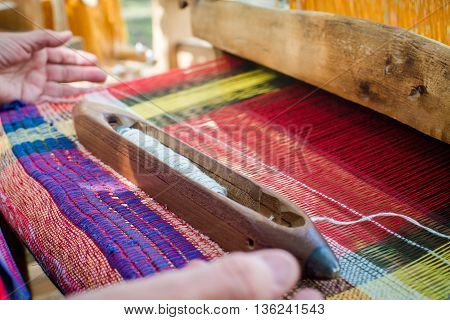 Weaving the threads on old wooden loom