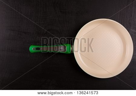 Ceramic Frying Pan on wooden background top view