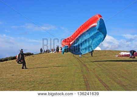 Paraglider launching wing on a hill top