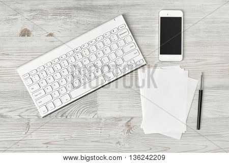 Workplace with keyboard, smarthphone, white sheets and pen on wooden surface in top view. Workplace of office man or information technology specialist. Office stuff. Readiness for the new. Beginning of something new. First work day. Uplifting mood. Coffee