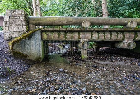 A walking bridge spans a small stream in the Pacific Northwest.
