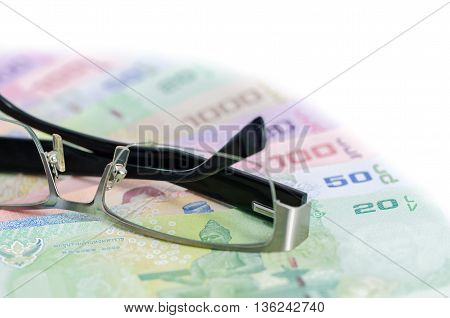 Glasses is place on thai baht banknote