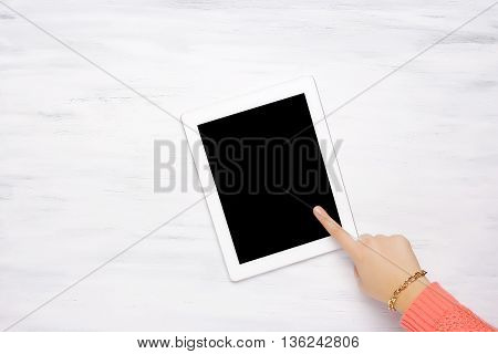 Top View Of A Woman's Hand Pointing To A Tablet.