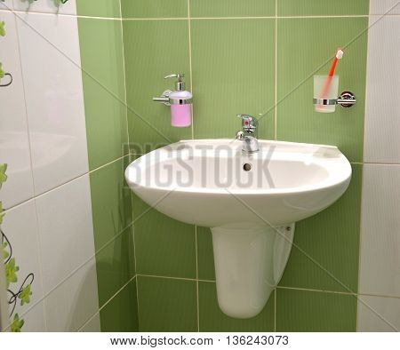 White wash basin soap container and toothbrush in glass in white green tiled bathroom