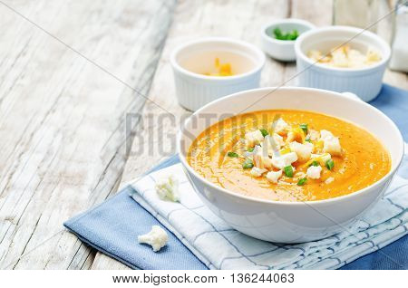 sweet potatoes cauliflower soup on white wood background