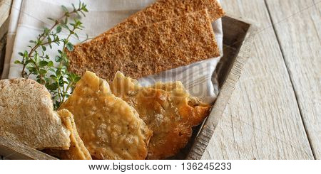 Dry bread with herbs on napkin and wooden tray