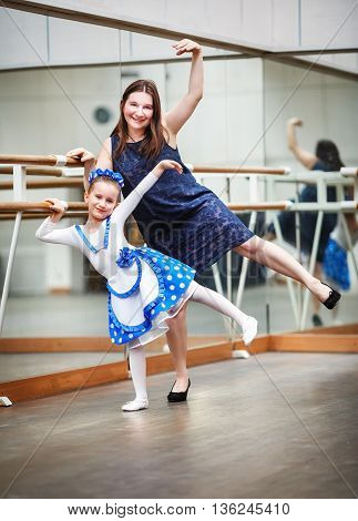 Mom and daughter posing at ballet barre. Happy family in a dance class. Mother and daughter practicing during class at a ballet school. Shallow depth of field. Selective focus.