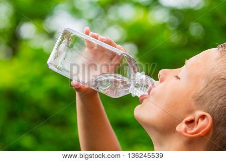 Young Boy Drinking Water From Bottle