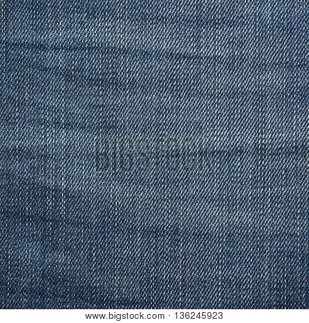 Fragment of a blue jeans cloth fabric material texture as an abstract background composition