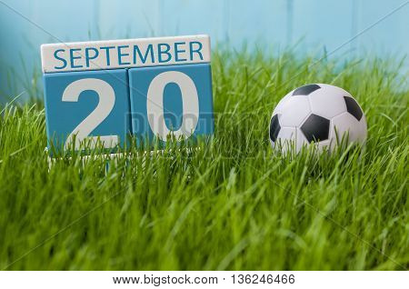 September 20th. Image of september 20 wooden color calendar on green grass lawn background. Autumn day. Empty space for text.