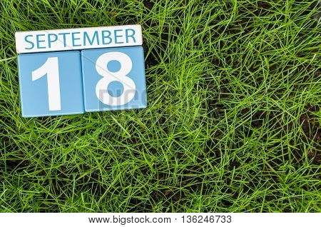 September 18th. Image of september 18 wooden color calendar on green grass lawn background. Autumn day. Empty space for text.