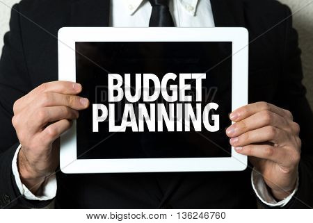 Business man holding a tablet with the text: Budget Planning