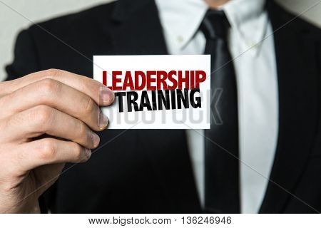 Business man holding a card with the text: Leadership Training