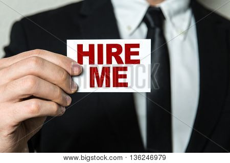 Business man holding a card with the text: Hire Me