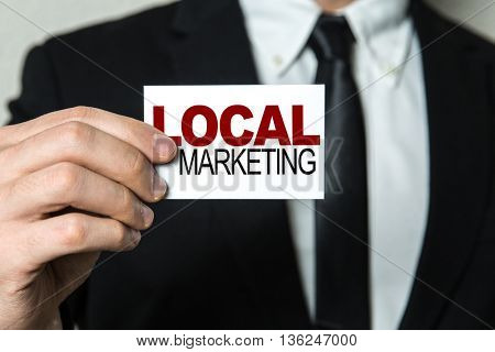 Business man holding a card with the text: Local Marketing