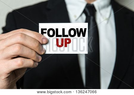 Business man holding a card with the text: Follow Up