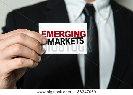 Business man holding a card with the text: Emerging Markets