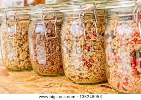 Homemade granola in jar on rustic kitchen table, healthy breakfast of oatmeal muesli, nuts, seeds and dried fruit