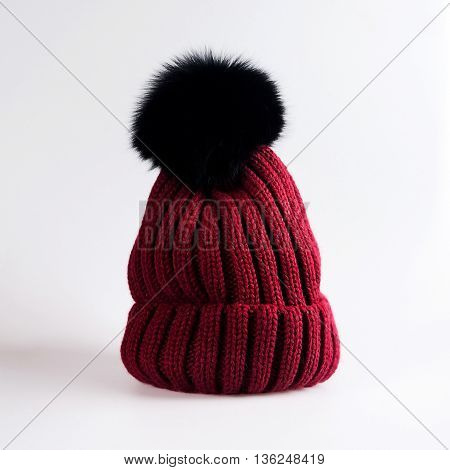 Knitted hat with bubo in a grey background